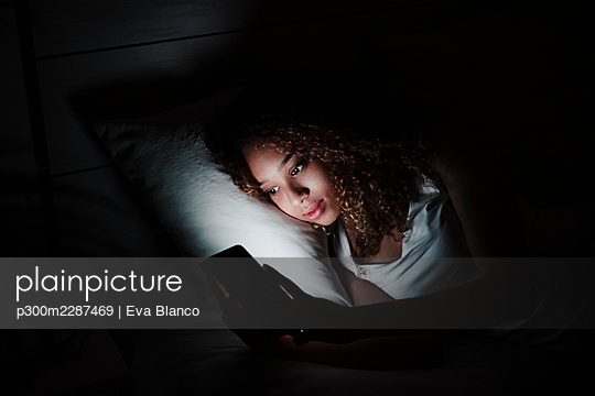 Woman using smart phone while lying on bed at night - p300m2287469 by Eva Blanco