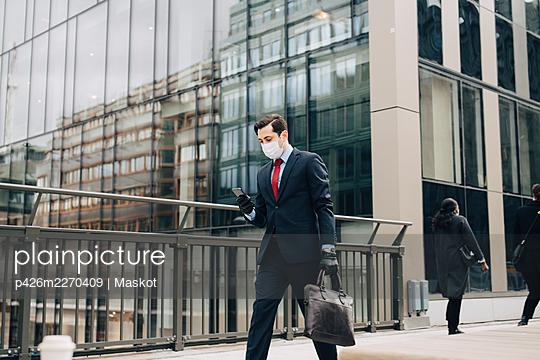 Male entrepreneur text messaging through smart phone while walking on bridge during pandemic - p426m2270409 by Maskot