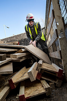Young man wearing hard hat and reflective vest standing on top of stack of recycled wood. - p1100m1575750 by Mint Images