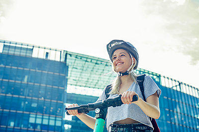 Portrait of smiling young woman with E-Scooter in the city, Berlin, Germany - p300m2139667 by Bernd Friedel