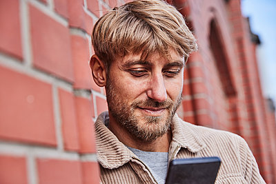 Man with blond hair using smart phone by building - p300m2274526 by Jo Kirchherr
