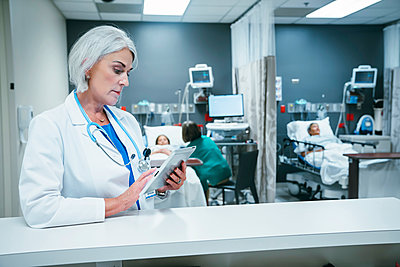 Doctor using digital tablet in hospital - p555m1521619 by FS Productions