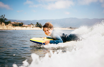 Portrait of young boy wearing wet suit, lying on surfboard, riding wave, Santa Barbara, California, USA. - p924m2208564 by JFCreatives