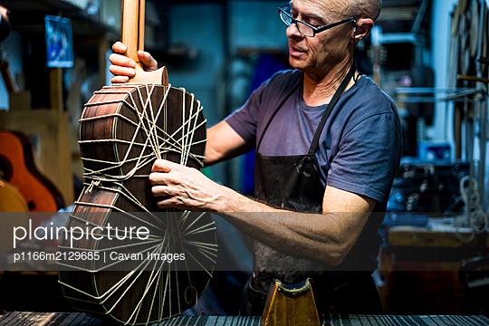 Luthier man making guitars in artisan workshop in Spain. - p1166m2129685 by Cavan Images