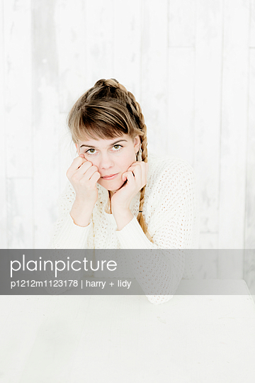 Junger Frau mit Zopf am Tisch - p1212m1123178 von harry + lidy