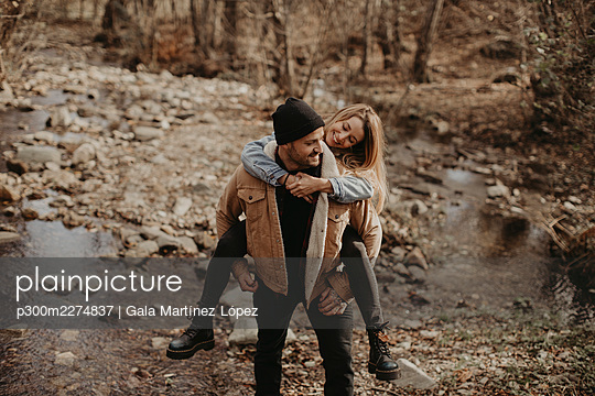 Man giving piggyback ride to girlfriend in forest  - p300m2274837 by Gala Martínez López