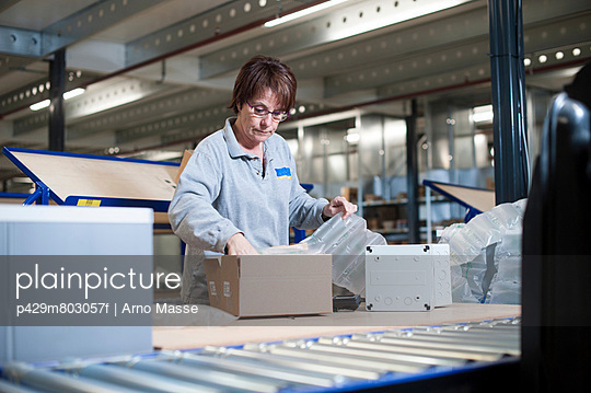 Female warehouse worker packing box for conveyor belt - p429m803057f by Arno Masse