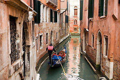 A gondola boat gliding down a small narrow waterway, between historic houses in the city of Venice.  - p1100m991390f by Mint Images