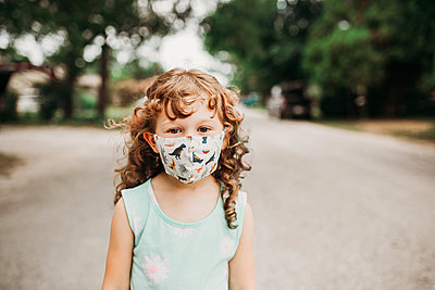 Young girl standing outside in neighborhood wearing homemade mask - p1166m2201631 by Cavan Images