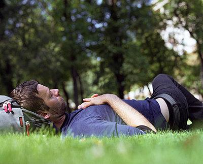 Junger Mann schläft in einem Park - p1409m1466419 von margaret dearing
