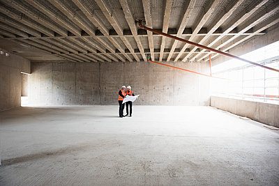 Two men with plan wearing safety vests talking in building under construction - p300m1460035 by Daniel Ingold