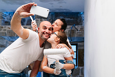 Happy family taking a selfie while painting the walls of her new house - p300m2166550 by Daniel González