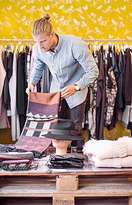 Male owner arranging cloths in clothing store - p426m977618f by Maskot
