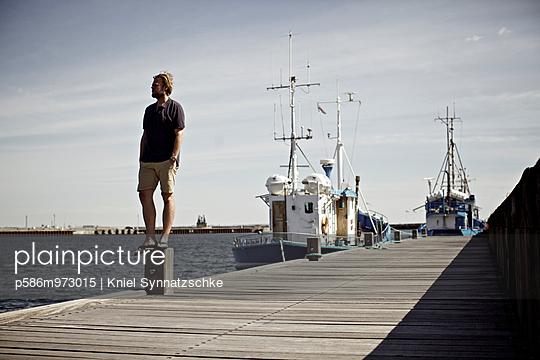 Ein Mann auf einem Pier blickt in die Ferne - p586m973015 von Kniel Synnatzschke