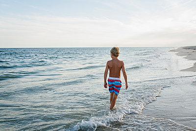 Rear view of shirtless boy walking at Tobay Beach in waves against sky - p1166m1544125 by Cavan Social