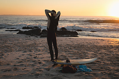 Rear view of surfer standing on beach during dusk - p1315m1565379 by Wavebreak