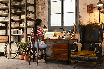Back view of young woman sitting at desk in a loft working on laptop - p300m1581388 by Bonninstudio