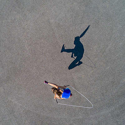Aerial view of young woman skipping rope, shadow - p300m2005375 von Stefan Schurr