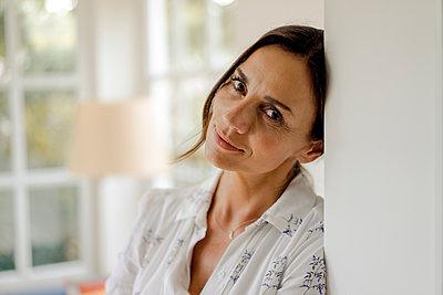 Portrait of mature woman leaning against doorframe - p300m2029669 von Kniel Synnatzschke