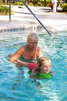 Grandmother and granddaughter in swimming pool - p312m672753 by Josefine Bolander