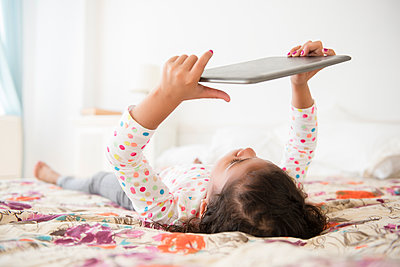 Mixed Race girl laying on bed using digital tablet - p555m1303874 by JGI/Jamie Grill