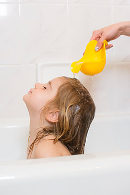 Caucasian mother rinsing hair of daughter in bathtub - p555m1304472 by JGI/Jamie Grill