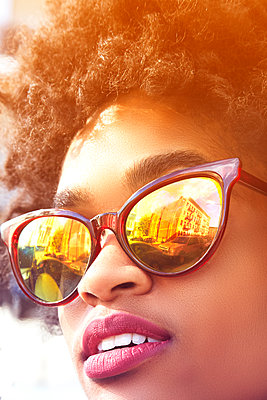 Close up portrait of young female fashion blogger with afro hair and mirrored sunglasses, New York, USA - p924m1422629 by Karen E. Evans