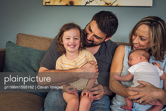 Happy family sitting on sofa at home - p1166m1555162 by Cavan Images