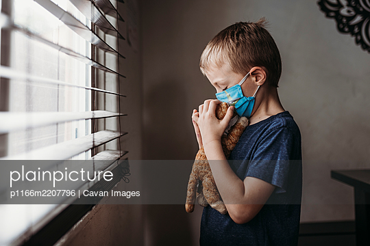 Side view of young school aged boy with mask on kissing stuffed animal - p1166m2207796 by Cavan Images