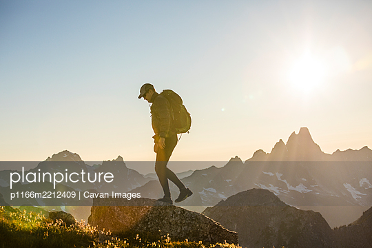 Back lit backpacker standing on mountain summit with scenic view - p1166m2212409 by Cavan Images
