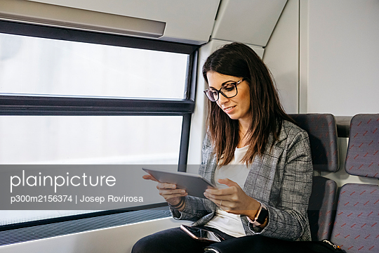 Brunette woman while traveling by train to work, with a tablet in her hands - p300m2156374 by Josep Rovirosa