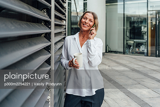 Businesswoman with mug talking on smart phone while standing by blinds at office park - p300m2294221 by Vasily Pindyurin