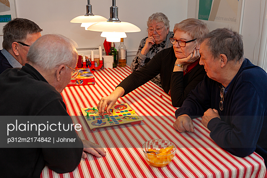 Senior people playing board game - p312m2174842 by Marie Linnér