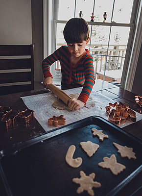 Boy rolling cookie dough on table during Christmas at home - p1166m1554998 by Cavan Images
