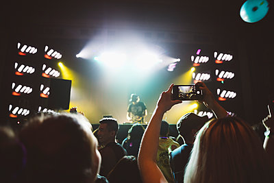 Woman with camera phone in crowd, videoing DJ on nightclub stage - p1192m1567138 by Hero Images