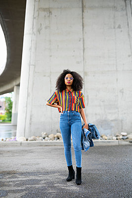 Portrait confident, cool young woman standing under overpass - p1192m2123472 by Hero Images