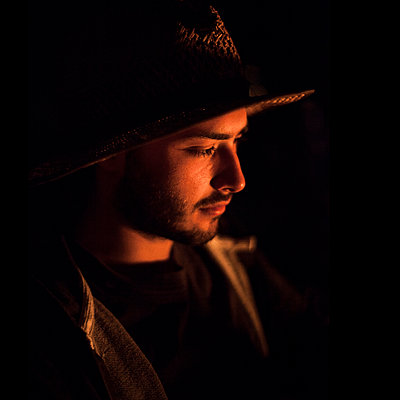 Young man with hat by the campfire - p1324m1165204 by Michael Hopf