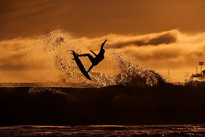 Surfer taking flight on a wave into the evening light - p1424m1501183 by Dylan Lucas Gordon