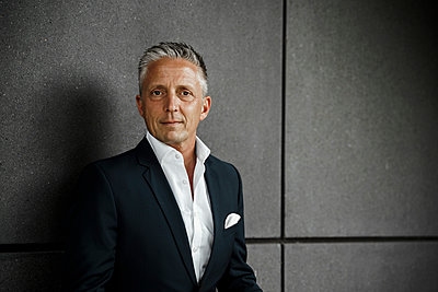 Gray haired male investor in front of gray wall - p300m2277455 by Sandro Jödicke