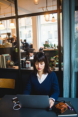 Confident businesswoman using laptop at desk in creative office - p426m2088969 by Maskot
