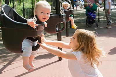 Caucasian girl pushing baby in swing - p555m1304469 by JGI/Jamie Grill