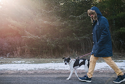 Man walking dog in countryside - p924m2068222 by Viara Mileva