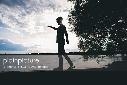 Full length of silhouette boy walking on retaining wall by lake against sky - p1166m2111823 by Cavan Images