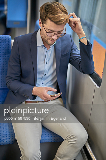 Businessman using smartphone in metro - p300m1587590 von Benjamin Egerland
