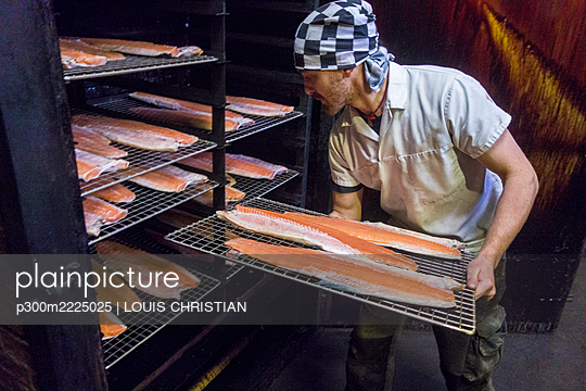 Manual worker inserting fish tray in smokehouse at food factory - p300m2225025 by LOUIS CHRISTIAN