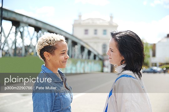 Lesbian women smiling while standing face to face on sunny day - p300m2290766 by Pete Muller