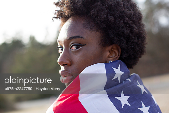 Woman with black ethnicity wrapped in American flag - p975m2247750 by Hayden Verry