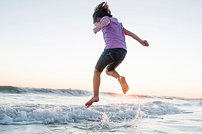 Low angle view of girl jumping on waves at beach against clear sky during sunset - p1166m1486187 by Cavan Images