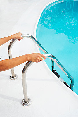 man grabbing the handrail of a swimming pool ladder - p1423m2073146 by JUAN MOYANO