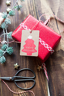 Christmas decoration and wrapped present on wood - p300m1189553 by Sandra Roesch